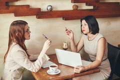 Two young caucasian businesswomen with laptop, notebook. Women in cafe Royalty Free Stock Photos