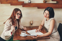 Two young caucasian businesswomen with laptop, notebook. Women in cafe Stock Photography