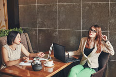 Two young caucasian businesswomen with laptop, notebook. Women in cafe Royalty Free Stock Photography