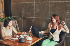 Two young caucasian businesswomen with laptop, notebook. Women in cafe Stock Photo