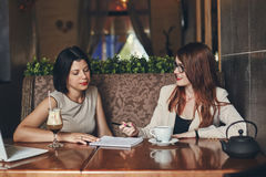 Two young caucasian businesswomen with laptop. Women in cafe Stock Images