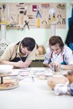Two Young Caucasian Ceramists Painting and Glazing Clay Crafts. Together in Workshop with Paintbrushes.Vertical Image Royalty Free Stock Photos