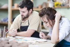 Two Young Caucasian Ceramists Painting and Glazing Clay Crafts. Together in Workshop with Paintbrushes.Horizontal Image Royalty Free Stock Photography