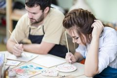 Two Young Caucasian Ceramists Painting and Glazing Clay Crafts. Young Caucasian Ceramists Painting and Glazing Clay Crafts Together in Workshop with Paintbrushes Stock Images