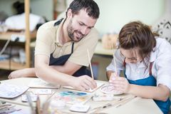 Two Young Caucasian Ceramists Painting and Glazing Clay. Pottering Ideas. Two Young Caucasian Ceramists Painting and Glazing Clay Crafts Together in Workshop Royalty Free Stock Photo