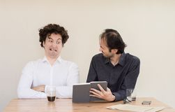 Two young Caucasian colleagues arguing at the table in the office with light background. stock photos
