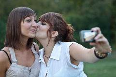 Two young caucasian female friends. Taking autoportraits of themselves kissing, having fun Stock Photos
