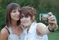 Two young caucasian female friends taking pictures. Two young caucasian female friends taking self-portraits of themselves kissing, having fun while outdoors Royalty Free Stock Images