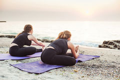 Two young caucasian females practicing yoga on beach Royalty Free Stock Images