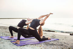 Two young caucasian females practicing yoga on beach Stock Images