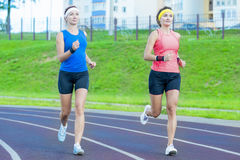 Two Young Caucasian Girlfriends in Athletic Sportswear Having Jogging Exercises Around the Sport Venue Royalty Free Stock Photo