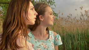 Two young Caucasian girls in dresses, hugging, admiring the sunset, nature.  stock video footage
