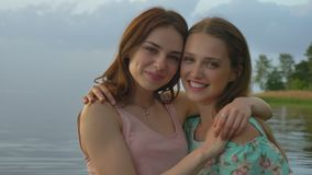 Two young Caucasian girls in dresses hugging on lake, laughing, smiling, nature in the background, looking at camera. Two young Caucasian girls in dresses stock video