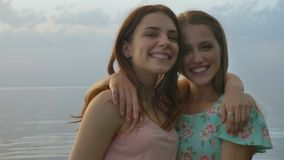Two young Caucasian girls in dresses hugging on lake, laughing, smiling, nature in the background, looking at camera. Two young Caucasian girls in dresses stock footage