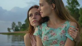 Two young Caucasian girls in dresses hugging on lake, nature in the background, looking at camera.  stock footage