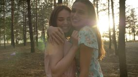 Two young Caucasian girls in dresses hugging in the woods, laughing, fooling around, looking at camera, nature in the. Two young Caucasian girls in dresses stock footage
