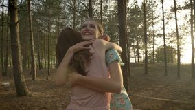 Two young Caucasian girls in dresses hugging in the woods, laughing, fooling around, nature in the background.  stock video