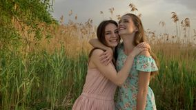 Two young Caucasian girls in dresses hugging in the woods, laughing, fooling around, nature in the background, looking. Two young Caucasian girls in dresses stock video