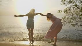 Two young Caucasian girls in dresses are running along the sand in the sea, laughing, hugging, nature in the background.  stock video