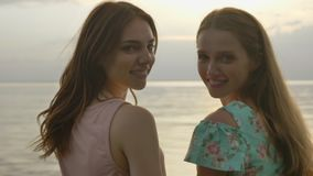 Two young Caucasian girls in dresses walking along shallow water at sunset, turn around and look at the camera.  stock video