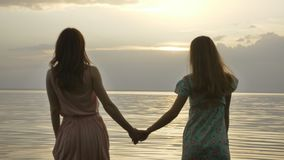 Two young Caucasian girls in dresses walking in shallow water at sunset.  stock video footage