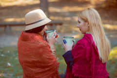 Two young caucasian girls enjoying coffee in autumnal park Stock Image