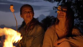 Two young Caucasian girls sit in the evening by the fire in nature, cooking marshmelow, smiling, eating.  stock footage