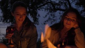 Two young Caucasian girls sit in the evening by the fire in nature, drink wine, smiling.  stock footage