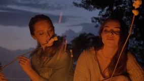 Two young Caucasian girls sit in the evening by the fire in nature, eating marshmelow, looking at an open fire, thinking.  stock video footage