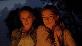 Two young Caucasian girls sit in the evening by the fire in nature, look into camera, portrait.  stock footage