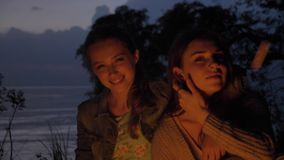 Two young Caucasian girls sit in the evening by the fire in the nature, looking at the camera, smiling, thinking.  stock video footage