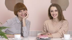 Two young caucasian girls sitting in a cafe and smiling, looking at the camera, portrait. Girls in a cafe concept. 60. Two young caucasian girls sitting in a stock video footage
