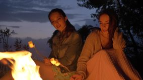 Two young Caucasian girls sitting by fire in evening in nature, preparing a marshmelow, looking at open fire, thinking.  stock video footage
