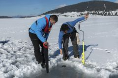 Two young Caucasian man looking at a hole on an ice on a frozen lake with saw and ice drill auger stock photo
