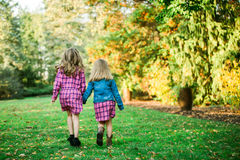 Two Young Caucasian Sisters Walking Away Holding Hands royalty free stock photography
