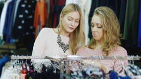 Two young Caucasian women choose things in women`s clothing store. Selection of women`s clothing. Two friends looking at the stand with underwear. A pleasant stock video footage