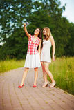 Two young caucasian women photographing themselves on small digital camera. Stock Photo