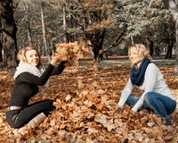 Two young caucasian women throwing yellow leaves stock image
