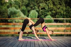Two young Caucasian women yogi doing balance back stretch acro yoga pose. Women doing stretching workout in park outdoors at sunse Royalty Free Stock Photography