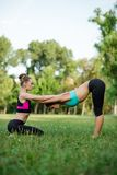 Two young Caucasian women yogi doing balance back stretch acro yoga pose. Women doing stretching workout in park outdoors at sunse Royalty Free Stock Images