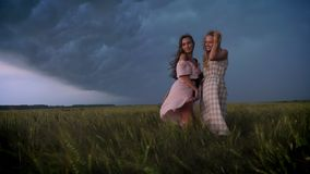 Two young charming girls in dresses is enjoing wind in field in rainy day in summer, freedom concept, flirt concept. Two young charming girls in dresses is stock footage
