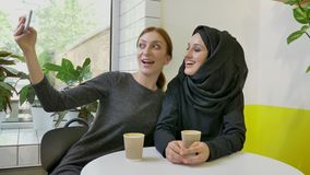 Two young charming womans sitting in cafe, one of them muslim woman in hijab, taking selfie with phone and posing. Smiling stock video