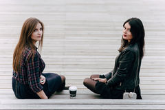 Two young charming women posing while sitting with take away coffee on a wooden stairs in the fresh air, Royalty Free Stock Images