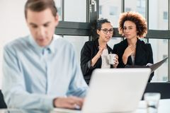 Two young cheerful female employees talking in the office Royalty Free Stock Image