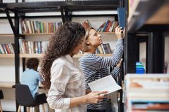 Two young cheerful female students in casual clothes standing near bookshelves in university library looking through