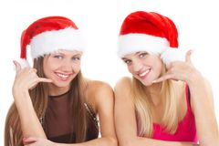Two young cheerful girls. In New Year's caps Royalty Free Stock Photos