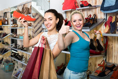Two young cheerful girls shopping together. Two young attractive girls shopping together in the fashion store Royalty Free Stock Photo