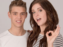 Two young cheerful people OK sign Royalty Free Stock Photography