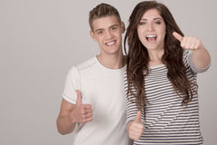 Two young cheerful people with thumbs up Stock Photo