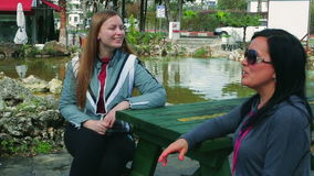 Two young cheerful woman sitting on a bench talking at a table in the park stock video footage